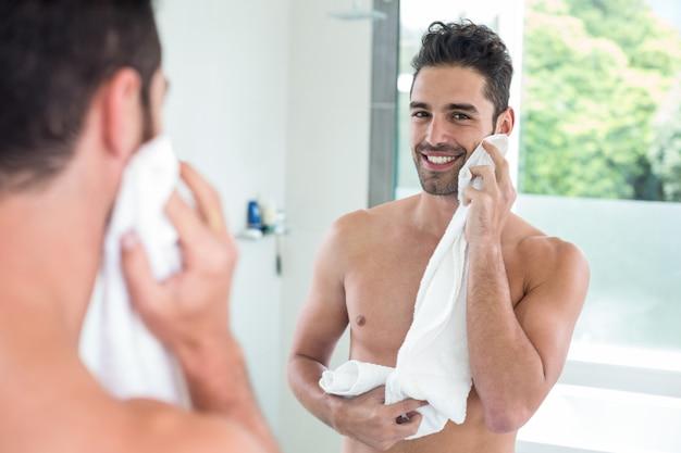 Gut aussehender mann, der gesicht beim schauen im spiegel abwischt