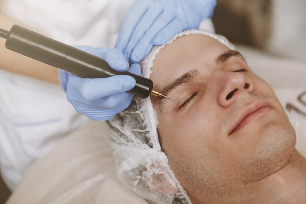 Gut aussehender mann, der gesichtshautpflegebehandlung erhält