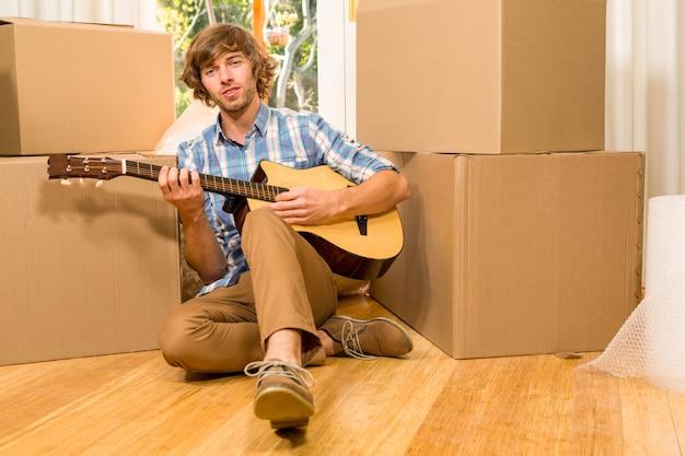 Gut aussehender mann, der gitarre mit beweglichen kästen in seinem neuen haus spielt