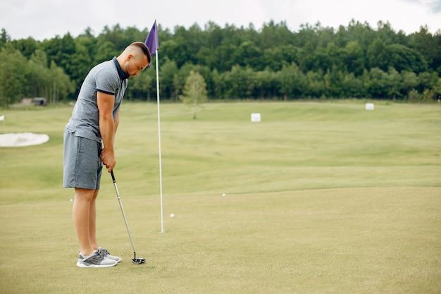 Gut aussehender mann, der golf auf einem golfplatz spielt