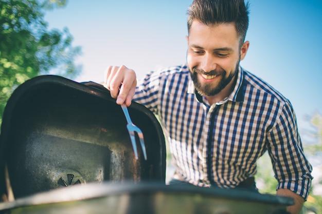 Gut aussehender mann, der grill für freunde vorbereitet. mann, der fleisch auf grill kocht - chef, der einige würste und pepperonis auf grill in den park im freien einsetzt - des essens im freien während der sommerzeit.