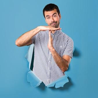 Gut aussehender mann, der heraus zeitgeste durch ein papierloch macht