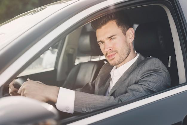Gut aussehender mann, der im auto betrachtet kamera sitzt