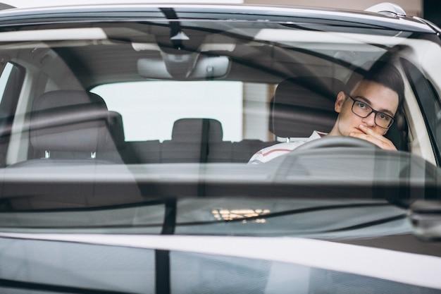 Gut aussehender mann, der im auto sitzt