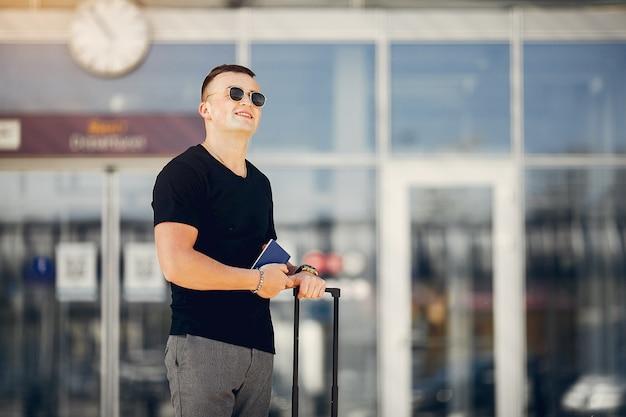 Gut aussehender mann, der im flughafen steht