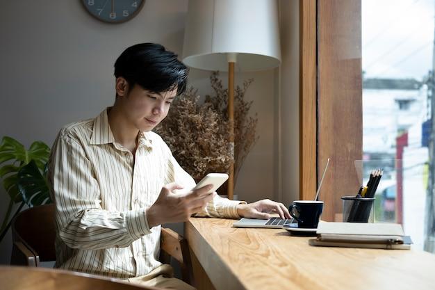 Gut aussehender mann, der im home office sitzt und smartphone verwendet.
