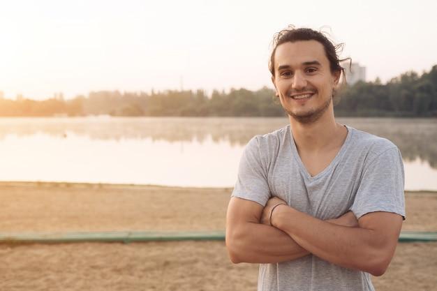 Gut aussehender mann, der im park lächelt
