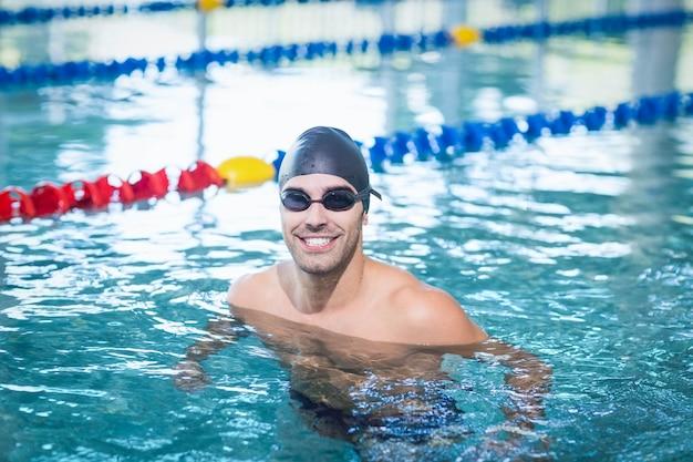Gut aussehender mann, der im pool schwimmt