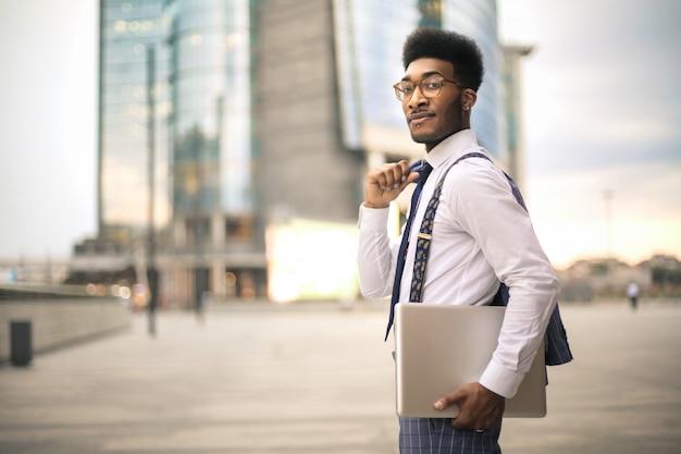Gut aussehender mann, der in die straße, seinen laptop tragend geht