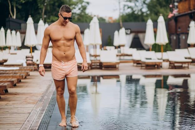 Gut aussehender mann, der in einem hotel am pool spazieren geht