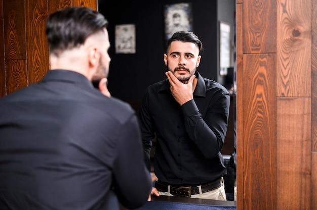 Gut aussehender mann, der in einem spiegel schaut