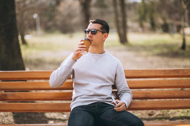 Gut aussehender mann, der in trinkendem kaffee des parks sitzt und telefon verwendet