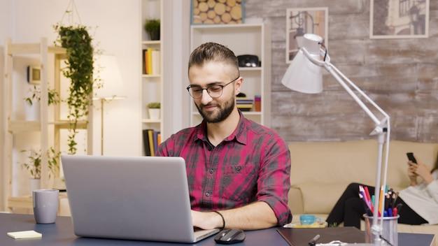 Gut aussehender mann, der lacht, während er im wohnzimmer am laptop arbeitet. freundin im hintergrund telefoniert.