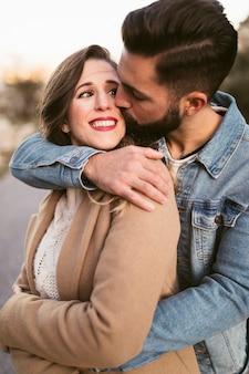 Gut aussehender mann, der lächelnde frau küsst