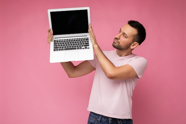 Gut aussehender mann, der laptop-computer hält und laptop-monitor im t-shirt auf isoliertem rosa hintergrund betrachtet.