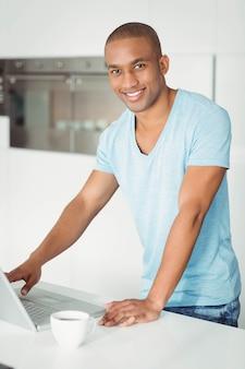 Gut aussehender mann, der laptop in der küche verwendet