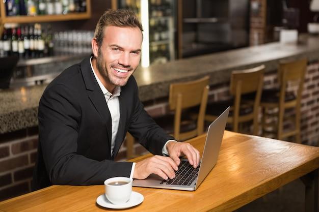 Gut aussehender mann, der laptop verwendet und einen kaffee trinkt