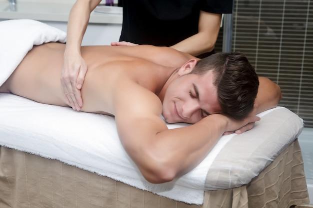 Gut aussehender mann, der massage im badekurort erhält