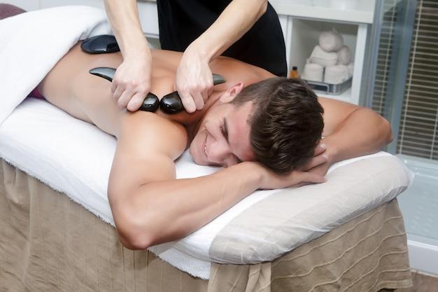 Gut aussehender mann, der massage mit heißen steinen erhält