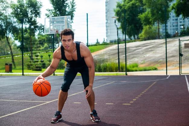 Gut aussehender mann, der mit dem basketballball spielt