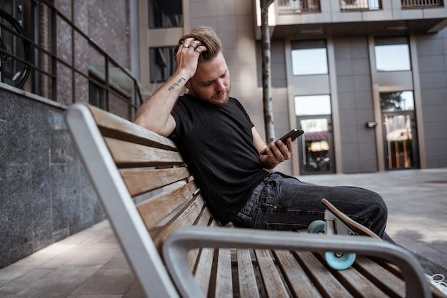Gut aussehender mann, der mit dem smartphone im internet surft, beiträge mag und sie über soziale netzwerke teilt, nachrichten auf der bank mit longboard mit nachdenklichem blick in schwarzer jeans und t-shirt liest