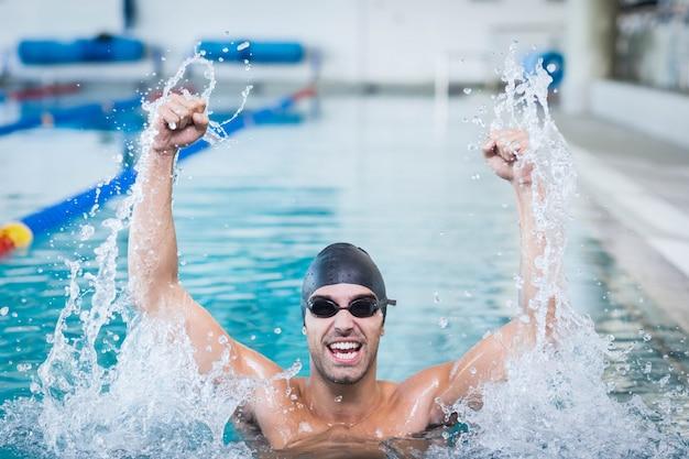 Gut aussehender mann, der mit den angehobenen armen im pool triumphiert