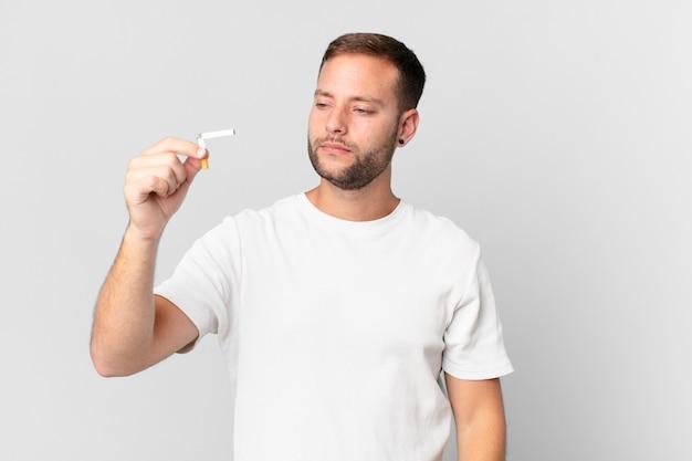 Gut aussehender mann, der mit einer kaputten zigarre aufhört zu rauchen