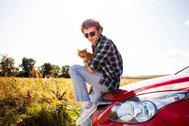 Gut aussehender mann, der mit einer katze aufwirft
