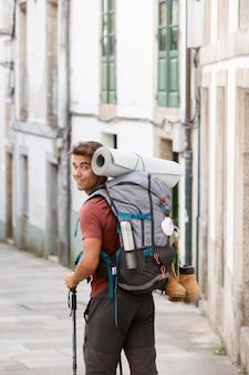 Gut aussehender mann, der mit seinem rucksack reist