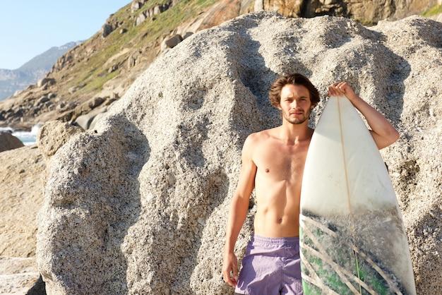 Gut aussehender mann, der mit surfbrett am strand aufwirft