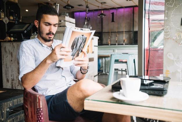Gut aussehender mann, der mit zeitschrift im café kühlt