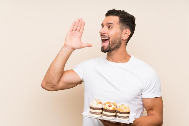 Gut aussehender mann, der muffinkuchen über lokalisiertem hintergrund hält