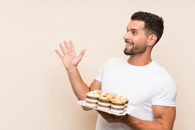 Gut aussehender mann, der muffinkuchen über lokalisierter wand mit überraschungsgesichtsausdruck hält