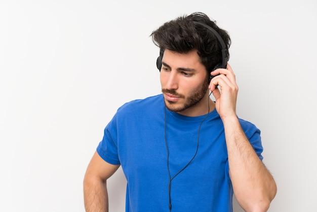 Gut aussehender mann, der musik mit kopfhörern hört