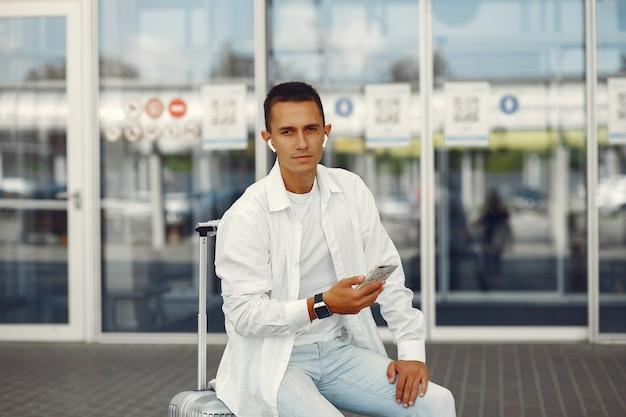 Gut aussehender mann, der nahe dem flughafen steht