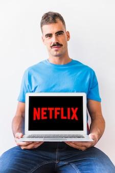 Gut aussehender Mann, der Netflix-Logo auf Laptop zeigt