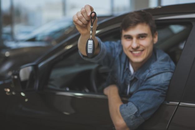 Gut aussehender mann, der neues automobil wählt, um zu kaufen