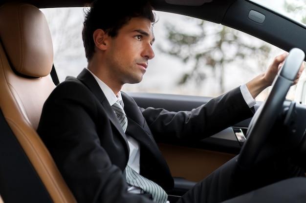Gut aussehender mann, der sein auto fährt
