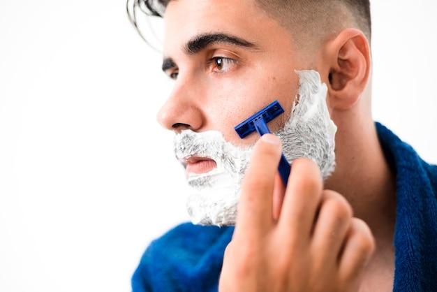 Gut aussehender mann, der seine bartnahaufnahme rasiert