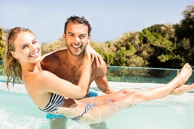 Gut aussehender mann, der seine freundin im pool trägt
