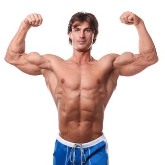 Gut aussehender mann, der seine muskeln zeigt