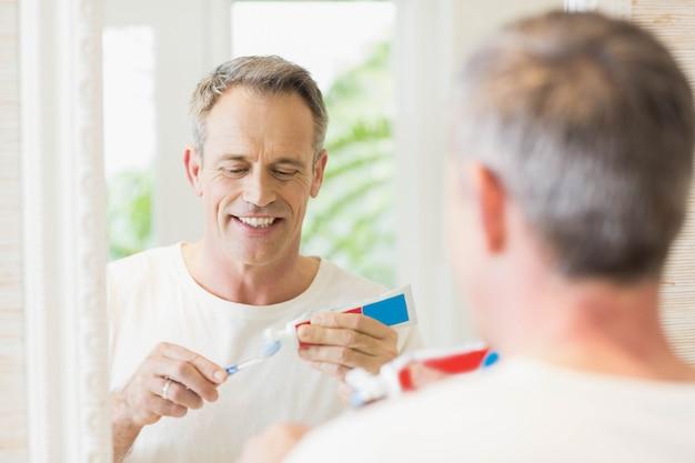 Gut aussehender mann, der seine zähne im badezimmer putzt