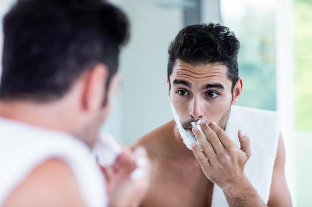 Gut aussehender mann, der seinen bart im badezimmer rasiert