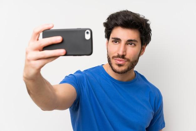 Gut aussehender mann, der selfie mit mobiltelefon macht