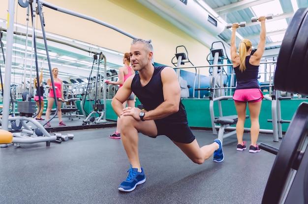 Gut aussehender mann, der sich in einem fitnesscenter ausdehnt, und zwei schöne frauen, die im hintergrund übungen mit hanteln machen