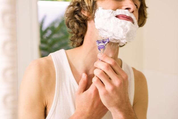 Gut aussehender mann, der sich zu hause im badezimmer rasiert