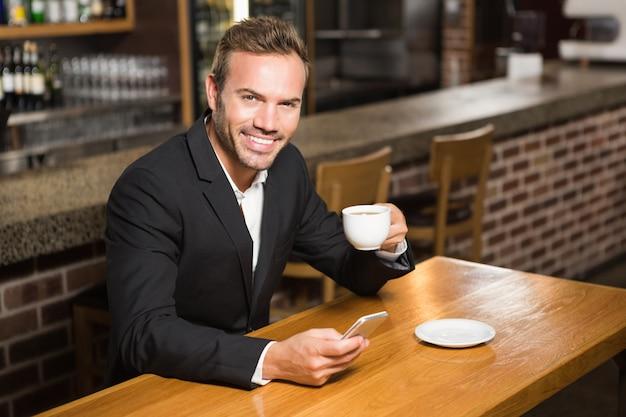 Gut aussehender mann, der smartphone betrachtet und einen kaffee trinkt