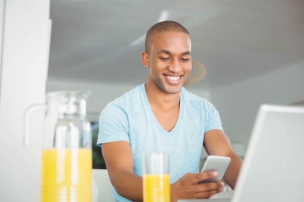 Gut aussehender mann, der smartphone in der küche verwendet
