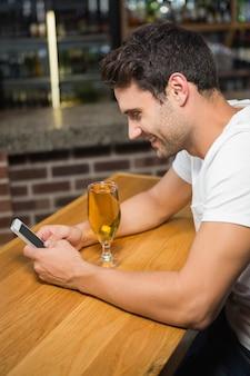 Gut aussehender mann, der smartphone verwendet und ein bier isst