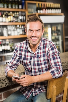 Gut aussehender mann, der smartphone verwendet